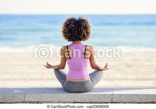 black woman afro hairstyle doing yoga in the beach rear view of