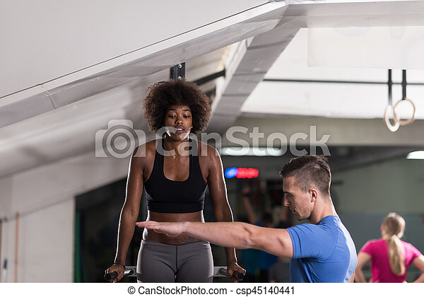 black woman doing parallel bars Exercise with trainer - csp45140441