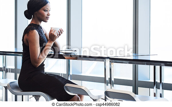 Black woman sitting on bar chair next to large window for Chair next to window