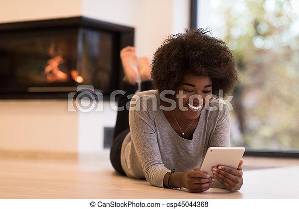 black women using tablet computer on the floor - csp45044368