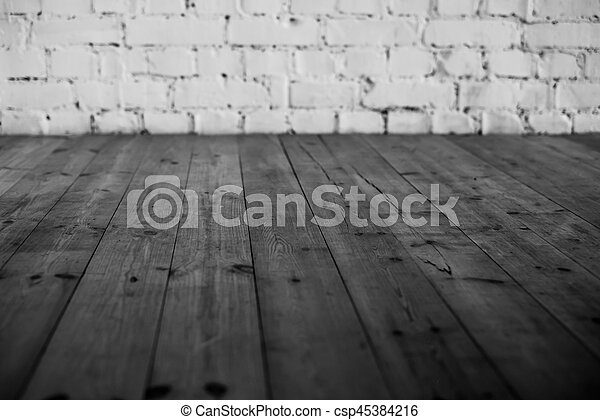 Black wooden floor and white brick wall background - csp45384216