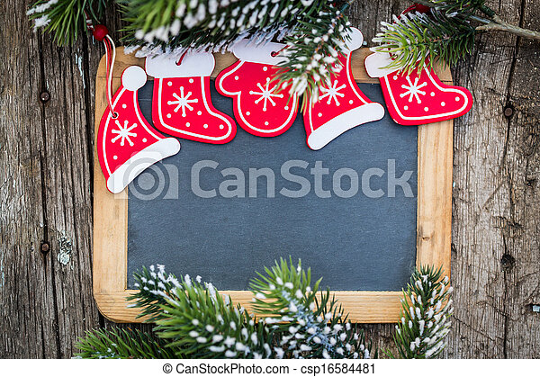 Blackboard blank framed in beautiful Christmas tree branches and decorations. Winter holidays concept. Copy space for your text - csp16584481