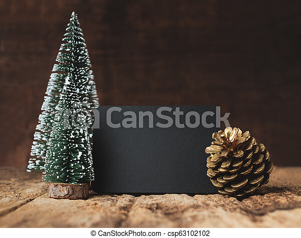 Blank blackboard with christmas tree and gold pine cone and snow falling on grunge wood table and dark brown wooden wall. winter holiday greeting card mock up template. - csp63102102
