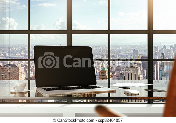 Blank laptop on a glass table in a modern office and city views from the windows - csp32464857