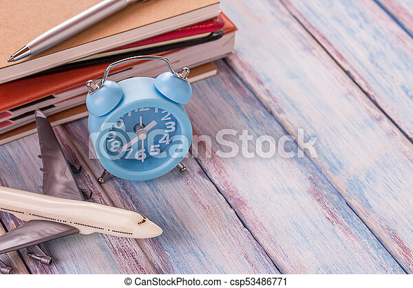 Blank notebook,airplane toy,pen and alarm clock on office desk with wooden background. - csp53486771