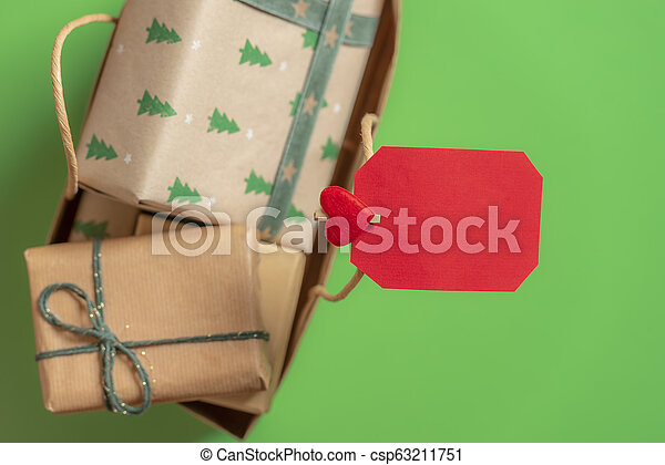 Blank paper note on a bag with Christmas gifts. Green background. Above view. - csp63211751