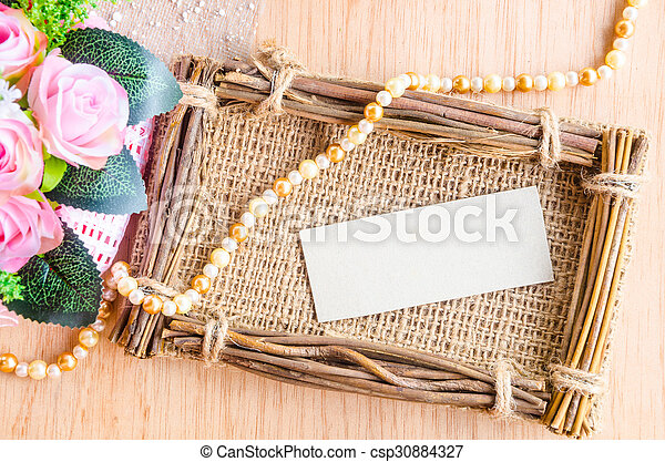 Blank paper tag in sack photo frame with beautiful flower - csp30884327