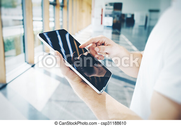 Blank tablet holding in male hands, he wearing a white shirt - csp31188610