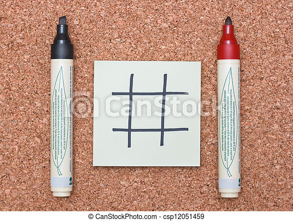 blank tic tac toe game on sticky note with red and black markers on cork background - csp12051459