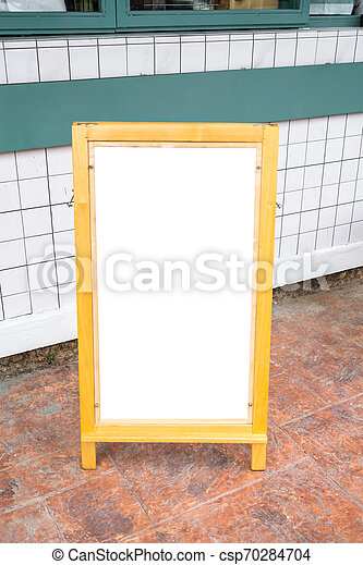Blank white menu stand on floor in front of restaurant - csp70284704