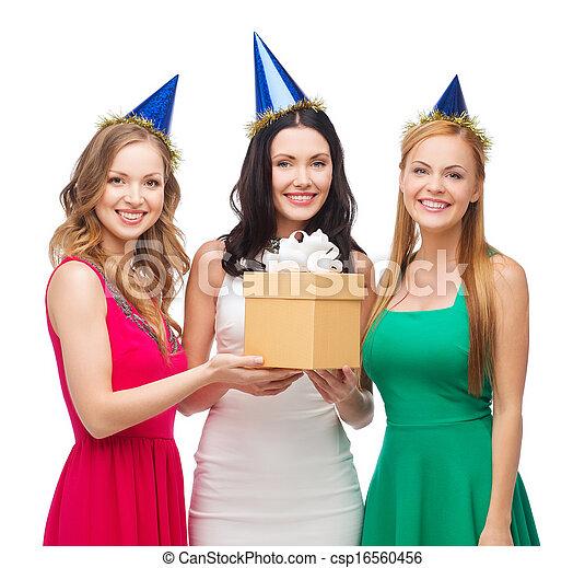 Drei lächelnde Frauen mit blauen Hüten mit Geschenkbox - csp16560456