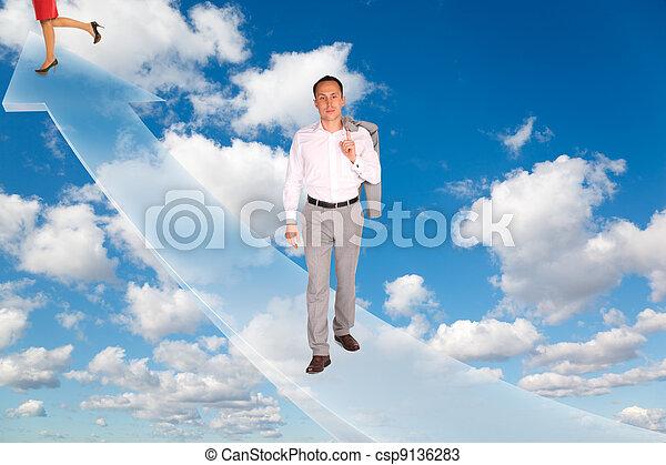 Mann und Frau auf Pfeil auf Weiß, fluffige Wolken im blauen Himmel kollabieren - csp9136283
