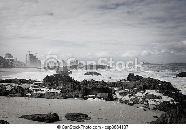 Bleak scene with smoggy clouds and construction next to a beautiful beach setting, being encroached on by development. - csp3884137