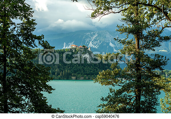 Bled castle between trees over the lake - csp59040476