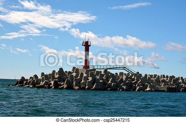 blocks and a lighthouse in the sea - csp25447215