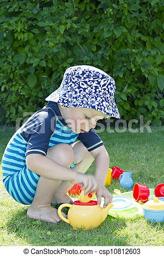 Blond boy in the garden playing with a plastic tea set - csp10812603