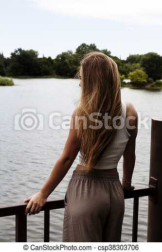 Blond Caucasian Teen Girl Standing At Rail Looking At River - csp38303706