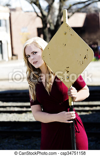 Blond Caucasian Woman In Red Dress Holding On To Yellow Sign - csp34751158