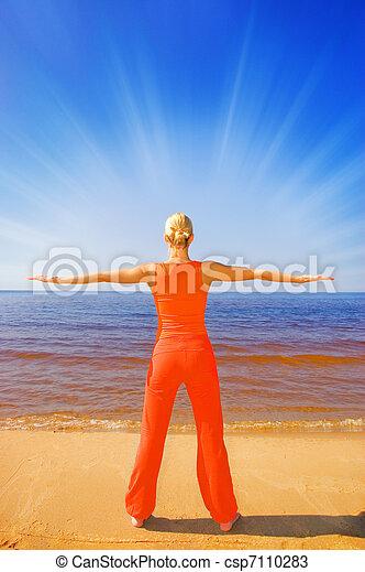 Blond girl meditating on the beach - csp7110283