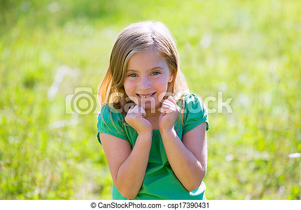 Blond kid girl excited gesture expression in green outdoor - csp17390431