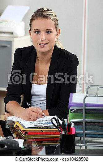 Blond receptionist sat at her desk - csp10428502
