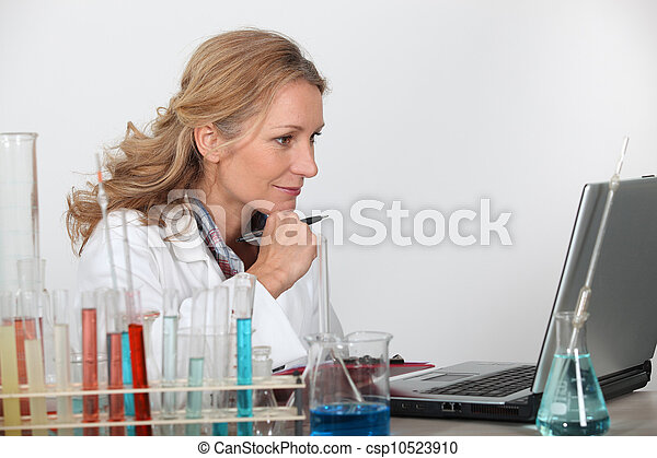 Blond researcher in lab using laptop computer - csp10523910