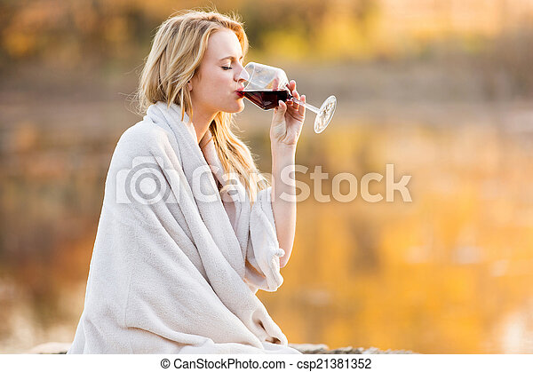 blond woman drinking red wine at sunset - csp21381352