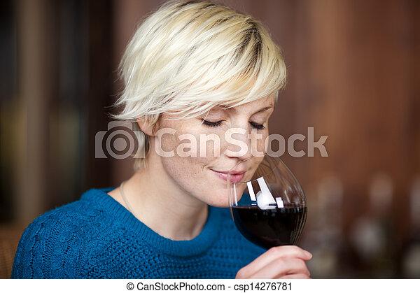 Blond Woman Drinking Red Wine In Restaurant - csp14276781