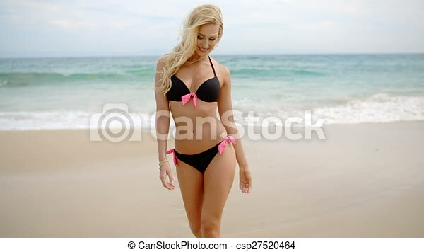 516eb337c99 Blond woman in bikini walking to camera on beach. Front view of blond  smiling woman wearing black bikini with pink bows walking towards camera on  sandy ...