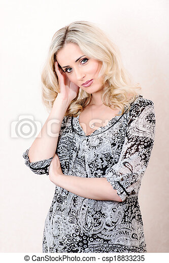 Blond woman in dress posing looking on camera - csp18833235