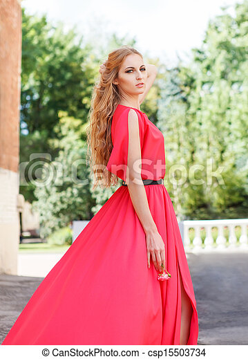 Blond woman in long red dress outdoors - csp15503734