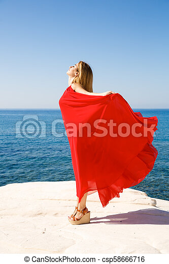 Blond woman in red - csp58666716