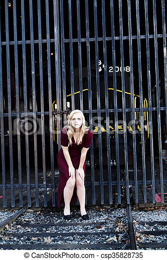 Blond Woman Red Dress Outdoors Railroad Tracks - csp35828735