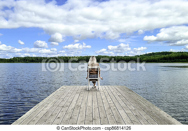 Blond woman sitting on white empty deck chair at the lake dock. - csp86814126