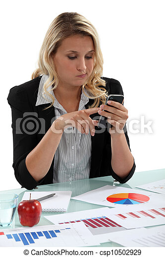 Blond woman with graphs on desk sending text message - csp10502929