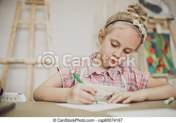 Blonde cute seven-year-old girl, draws at the table in the creative studio - csp60074167