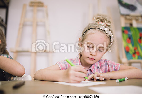Blonde cute seven-year-old girl, draws at the table in the creative studio - csp60074159