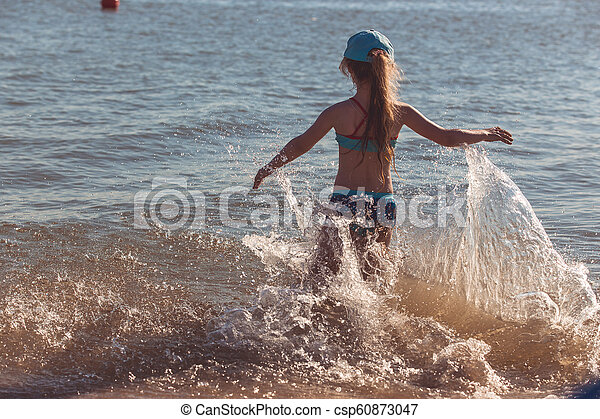 Blonde cute seven-year-old girl having fun and having a good time at the sea during the holidays - csp60873047