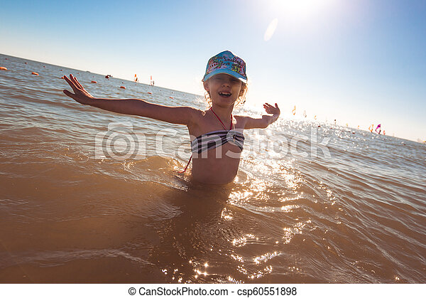 Blonde cute seven-year-old girl having fun and having a good time at the sea during the holidays - csp60551898