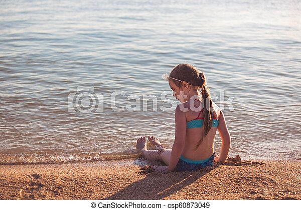 Blonde cute seven year old girl sitting on the beach during vacation - csp60873049