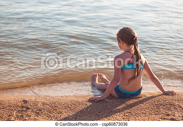 Blonde cute seven year old girl sitting on the beach during vacation - csp60873036
