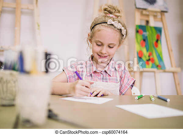 Blonde cute smiling seven-year-old girl, draws at the table in the creative studio - csp60074164