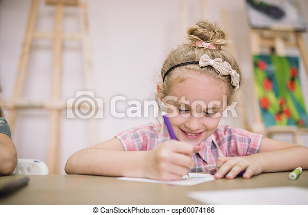 Blonde cute smiling seven-year-old girl, draws at the table in the creative studio - csp60074166