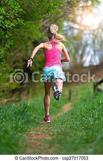 Blonde girl athlete running in a trail into the woods - csp27017053