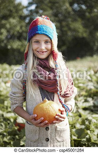 Blonde girl holding pumpkin in hands - csp45001284