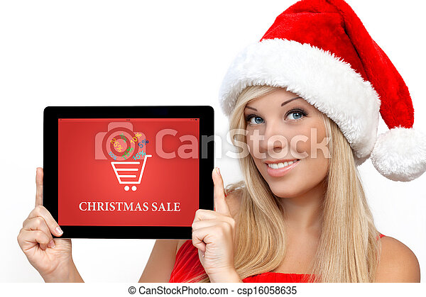 blonde girl in a red Christmas hat on New Year, holding tablet computer with christmas sale on a screen - csp16058635