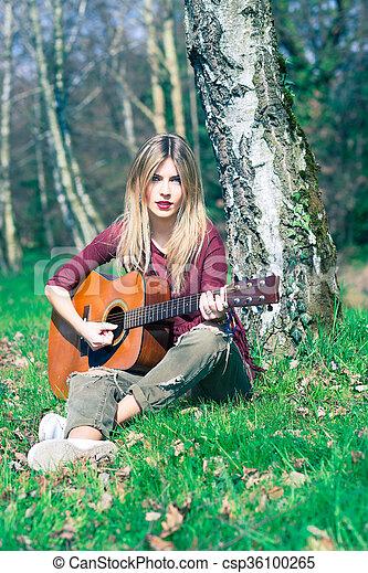 blonde girl plays guitar in the meadow in summer