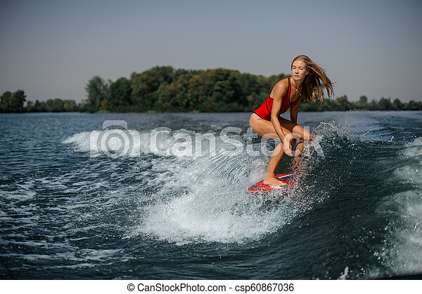 Blonde girl riding on the red wakeboard - csp60867036