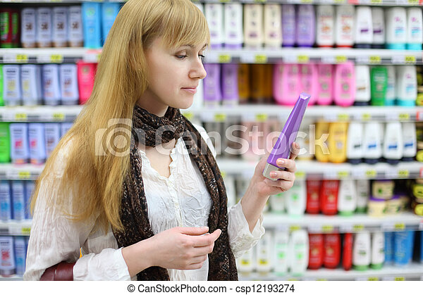 Blonde girl wearing white shirt chooses shampoo in large store; shallow depth of field - csp12193274