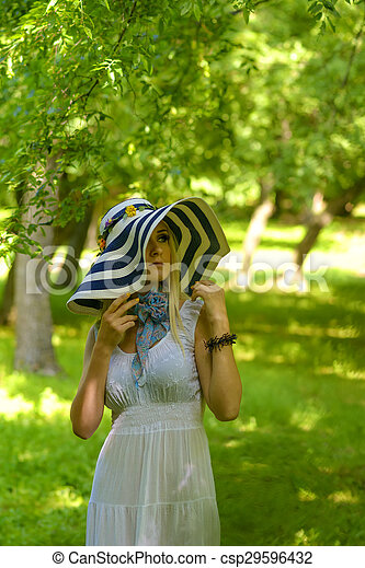 blonde girl with big summer hat - csp29596432